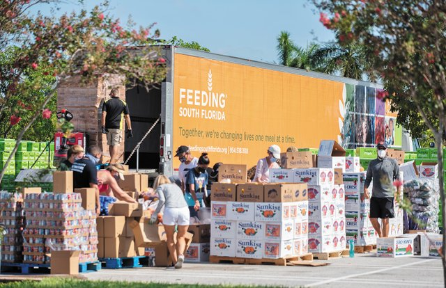 Volunteers preparing food at a food distribution at the Palm Beach Outlets in West Palm Beach on July 21, 2020.jpg
