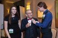 2-Holocaust survivor Saul Dreier (center) is pinned with a boutonniere by Spanish River High School student Natalia Aharon (left) and Park Vista High School student Maxwell Tammany (right).jpg