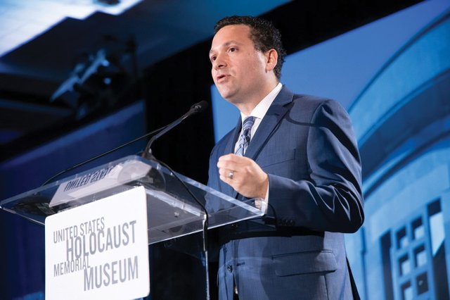4-Robert Tanen, Southeast Regional Director for the United States Holocaust Memorial Museum, delivers the institutional message from the stage.jpg